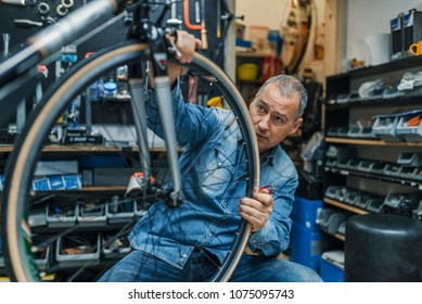 Bike mechanic repairing a wheel. Mechanic or serviceman installing wheel on a bicycle in workshop. Mature man working in a biking repair shop