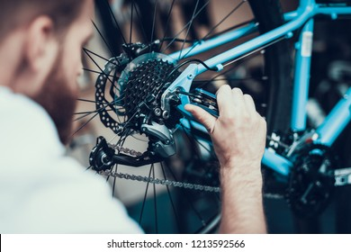 Bike Mechanic Repairs Bicycle in Workshop. Closeup Portrait of Young Blurred Man Examines and Fixes Modern Cycle Transmission System. Bike Maintenance and Sport Shop Concept