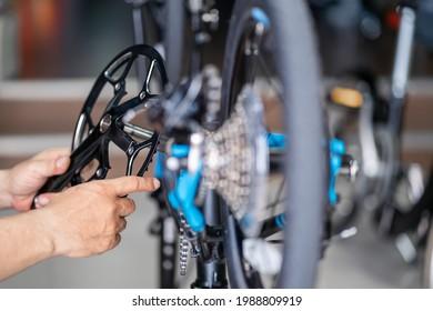 Bike mechanic repairs folding bicycle in Workshop. install Crankset Chainring,  Bicycle Maintenance and Repair concept
