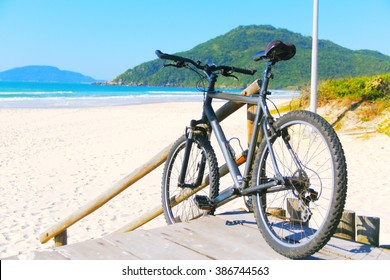 Bike on beach. Bike leaning at wooden fence at the beach,  Southern Brazil