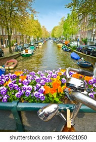 Bike on a bridge with flowers and canal. Amsterdam, Netherlands. Focus on the flowers.