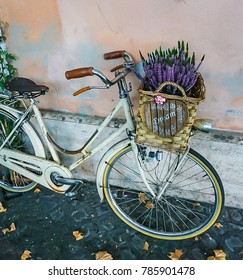 A bike on coblestone sidewalk with basket of Lavender flowers and dream sign