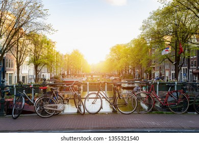 Bike over canal Amsterdam city in Netherlands with view on river Amstel during sunset.