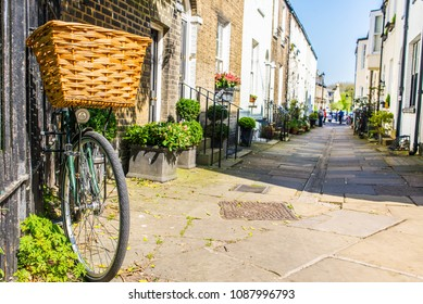 Bike parked against a wall in a small traditional British street mews with classic English Victorian houses in a sunny day