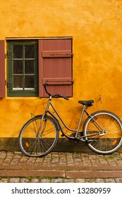 Bike parked in front of a rustic cottage