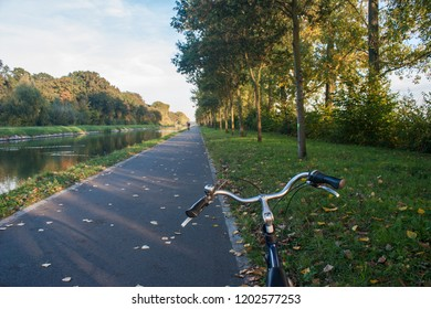 A bike parked on the side of the Dijle River Bike Path between Leuven and Mechelen, Belgium, on a sunny day in autumn with colorful foliage and reflections.