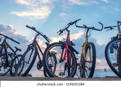 bike parking, row of bikes on the beach wit blue cloudy sky background