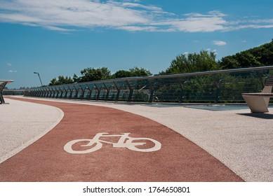 Bike path with of bicycle symbol. Pink bike lane with non-slip acrylic coating on city footbridge