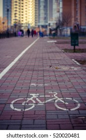 Bike path in the city, the outline of a Bicycle painted on the pavement against the backdrop of urban houses