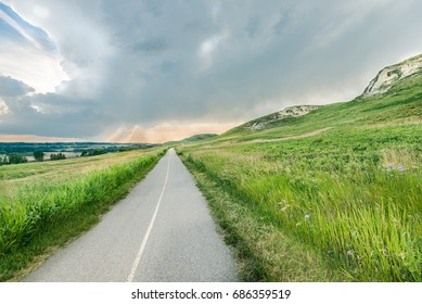 Bike path heading towards gorgeous evening sky of Southwestern Alberta. Surrounded by grasslands and rolling hills.