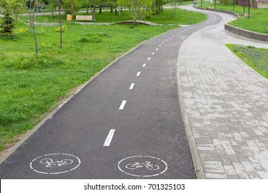 Bike path in the park. A bicycle road in a cozy park.