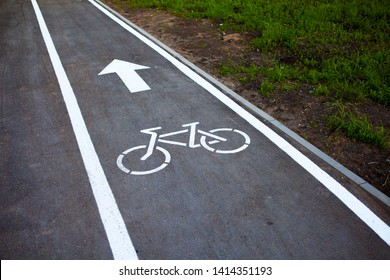 Bike path. Sign white paint on the pavement. Summer. bicycle traffic sign painted on the floor