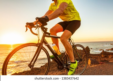 Bike race at sunset road biking cyclist riding bicycle outdoor with sun flare closeup of legs and yellow cycle shoes.