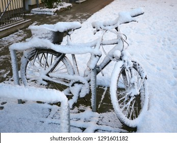 Bike at bike rack, snowed, covered in snow