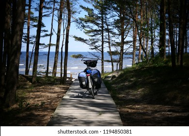 Bike ride into the blue - A travel bike with two panniers stands on a wood path in the forest. The path leads directly to the beach.