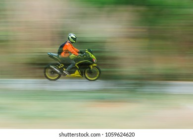Bike rider in motion blur  panning photo of unidentified people riding motorcycle.