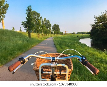 Bike rides along the bike path towards the mill. Typical Dutch landscape. Bicycles and mills are symbols of the Netherlands. Environmental protection transport.