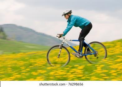 Bike riding - woman downhill on bike in dandelion meadow (intentional motion blur)