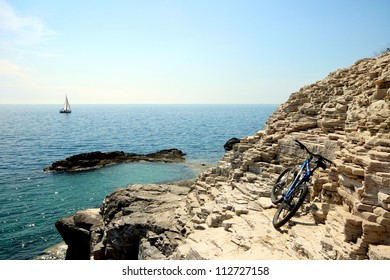 Bike, rocks and boat Description: Bicycle and sailboat on the coastline