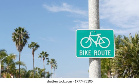 Bike Route green road sign in California, USA. Bicycle lane singpost. Bikeway in Oceanside pacific tourist resort. Cycleway signboard and palm. Healthy lifestyle, recreation and safety cycling symbol.
