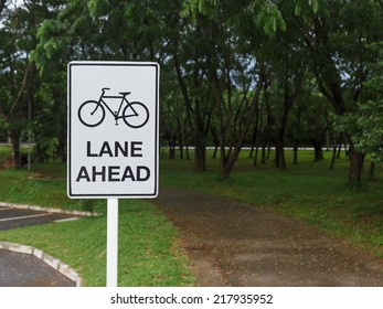 Bike route sign on white plate in the garden.