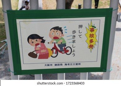 A bike safety warning sign tied to metal railings. Osaka, Japan - 6th April 2016
