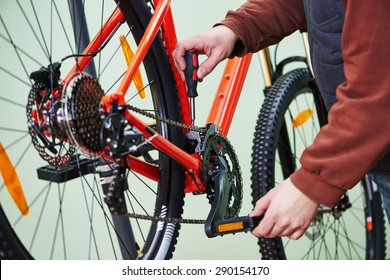 Bike service: mechanic serviceman repairman tuning and assembling or adjusting bicycle chain in workshop