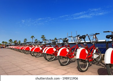 Bike Sharing in Barcelona Spain / Long row of red and white bicycles (public bikes) near the harbor in Ronda Litoral, Barcelona - Spain