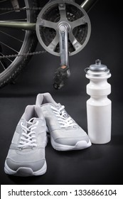 bike with sneakers and a bottle of water on a black background