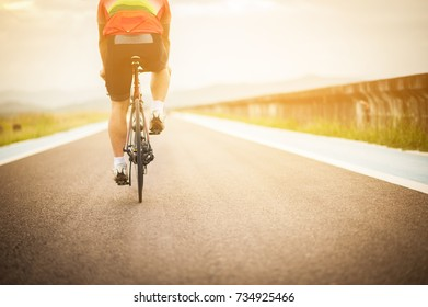 Bike at the summer sunset on the road. Cycle closeup wheel on blurred summer background.