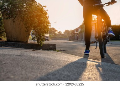 Bike at the summer sunset on the tiled road in the village. Cycle closeup wheel on road village background. Cycling down the street to work at summer . Bicycle and ecology lifestyle concept. - Image