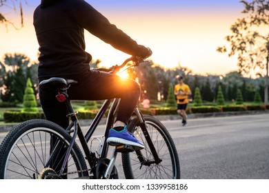 Bike at the summer sunset on the tiled road , Exercising of bike on road in park background. Cycling down the street to work at summer sunset, sunrise. Bicycle and ecology lifestyle concept. - Image