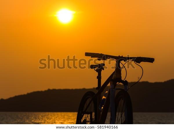 Bike and Sun set in orange background.