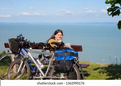 Bike tourism around lake Balaton in Hungary - young woman with bikes sitting on a bench at the beach of lake Balaton