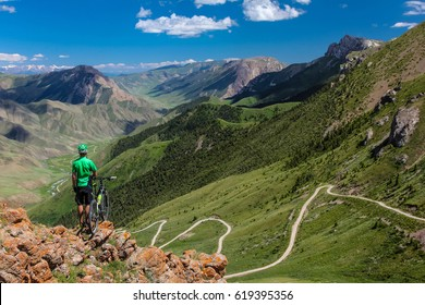 Bike trip. A man with a bicycle on a mountain pass. Kyrgyzstan