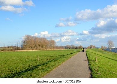 Bike and walking path over an embankment along a wide river in the Netherlands. It's a sunny day in the winter season and in the background an unknown elderly couple is strolling together.