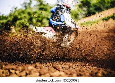 Biker accelerating during a motocross race with lots of mud and debris