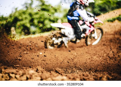 Biker accelerating during a motocross race with flying mud and debris