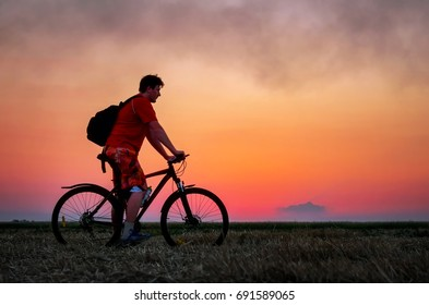 Biker with bicycle on the field during sunrise