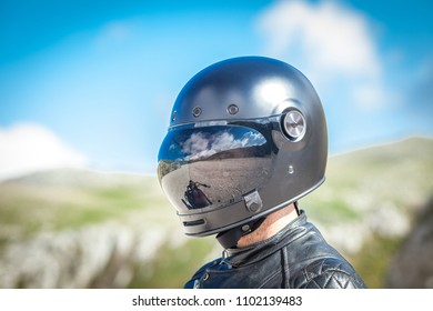 Biker with black helmet reflected in the visor a desolated landscape in front of his. Blue sky background. Post apocalyptic concept