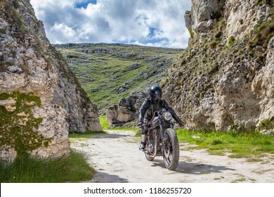 Biker with black leather clothes, ride his custom rat motorcycle in a desolated mountain land. Post apocalyptic concept