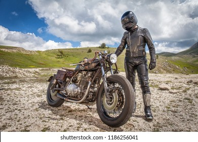 Biker with black leather clothes, standing near his custom rat motorcycle in a desolated mountain land. Post apocalyptic concept