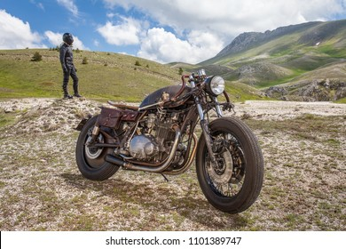 Biker with black leather suit and mask stay on a custom special rat motorbike. Post apocalyptic concept