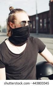 Biker in black t-shirt posing holding his helmet