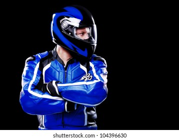Biker in blue jacket and helmet on black background looking to the copy space area