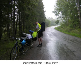 Biker with camping equipment stops beside the road in rainy summer day trip