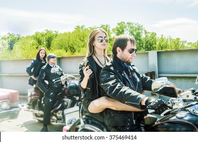 Biker Couple with motorcycle Chopper style Man and woman ride with high speed Cute girl wear black leather jacket and stylish sunglasses against urban background Gang of groups of armed people