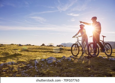 Biker couple with mountain bike pointing in distance at countryside