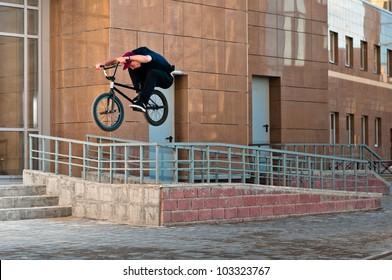 Biker doing high rail hop trick on bmx, front view