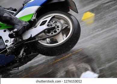 Biker doing some curves in the rain during a safety instruction day